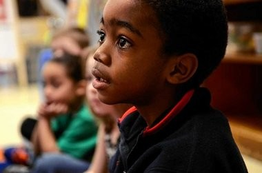 Aiden Drummond listens to his teacher during his pre-k classroom's morning meeting at Syracuse's Huntington School on Friday. The meeting included some arithmetic, days of the week review and rhyming exercises.