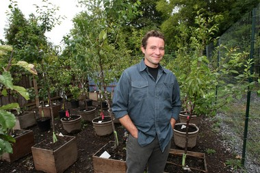 Sculptor Sam Van Aken, an associate professor at Syracuse University, poses for a photo in 2011 with the trees he was developing to bear 40 different varieties of fruit.