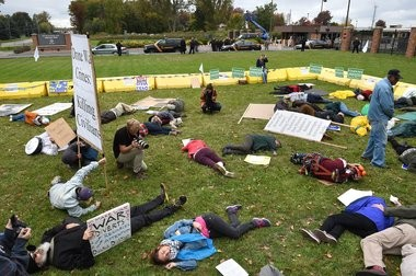 """Anti-drone demonstrators stage a """"die-in,"""" where participants simulate being killed or injured by a drone strike."""
