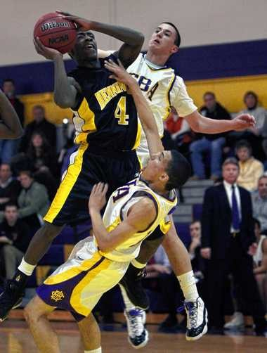 The late Kihary Blue (left) of Henninger High School, jumps forward for a shoot and collides with Stefan Thompson of CBA as Mike Kitts of CBA defends behind during the first quarter of the game at CBA high school in 2009. Katko's team prosecuted Kahari Smith, who was sentenced in March to 35 years in connection with Blue's death.