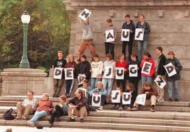 "Students from Husum, Germany, on a 14-day tour of the United States, stopped in Syracuse to send a message home via the syracuse.com camera pointed at Clinton Square. They're holding letters to spell ""House of Youth"" and the town's name below it."