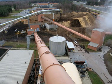 This Nov. 12, 2014 photo shows a view from the roof of the ReEnergy biomass power plant, overlooking wood chip piles and conveyors, at Fort Drum, N.Y. The biomass power plant is part of a military-wide initiative to put green energy systems on installations nationwide.