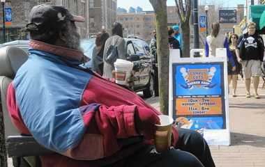 Gertis McDowell sitting on Marshall Street outside Campus Cuts barber shop in 2014. McDowell died on Jan. 7 at age 67.