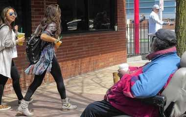 """Gertis McDowell greets passers-by on Marshall Street in this 2014 photo. He was known for greeting females with """"pretty lady"""" or """"pretty girl"""" and greeting males as """"big papa."""""""