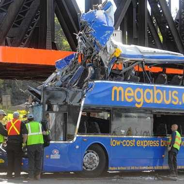 Investigators examine the area around the bus driver at the scene of a fatal Megabus accident, after the bus was pulled upright. The bus hit the Onondaga Lake Parkway railroad bridge abutment at around 2:30 a.m. Saturday and rolled onto its side. Photo by Peter Chen/The Post-Standard.