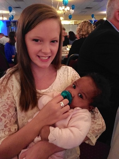 Erin Byrnes holds a baby at a gala for Joseph's House Sept. 24. Byrnes won a $70,000 car and donated it back to the charity.