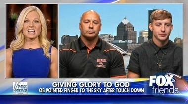 "Mexico High School quarterback Dante Turo, right, and his father Geno Turo, center, appeared Thursday on the popular conservative morning talk show ""Fox & Friends."" They talked about Dante Turo being flagged when he made a religious gesture after scoring a touchdown."