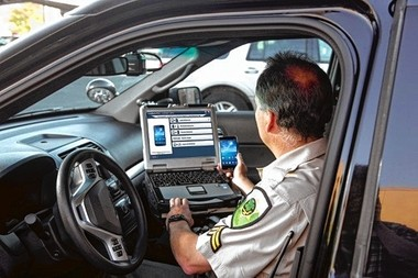 """In this marketing photo provided by Cellebrite, an officer uses software in his laptop to access the content of a suspect's cell phone. Cellebrite is developing technology that will also allow police investigating a motor vehicle accident to see if the driver had been using their cell phone immediately prior to the crash. A bill pending before the New York State Legislature called """"Evan's Law"""" would automatically allow police investigating crashes to check motorists' phones for usage."""