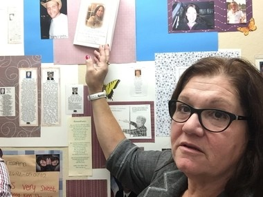 Kim Bermel, a facilitator at Hope for Bereaved in Syracuse, touches an obituary for a woman who died of a recent overdose. The walls at Hope for Bereaved are covered in bulletin boards with death announcements and obituaries, including for victims of heroin overdoses.