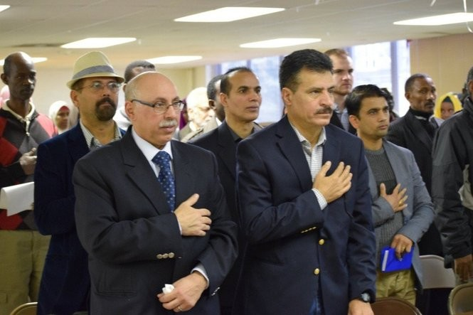 Hadith Alnoamy, right, came to Syracuse from Iraq and earned his U.S. citizenship. He voted for the first time in the 2016 presidential election. At left is Waleed ALsaadi, also from Iraq. They said the Pledge of Allegiance before a candidate forum in Syracuse in October.