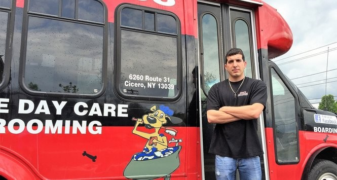 Carmen Cesta, owner of Carm's Dog House, stands near one of his mobile grooming buses.