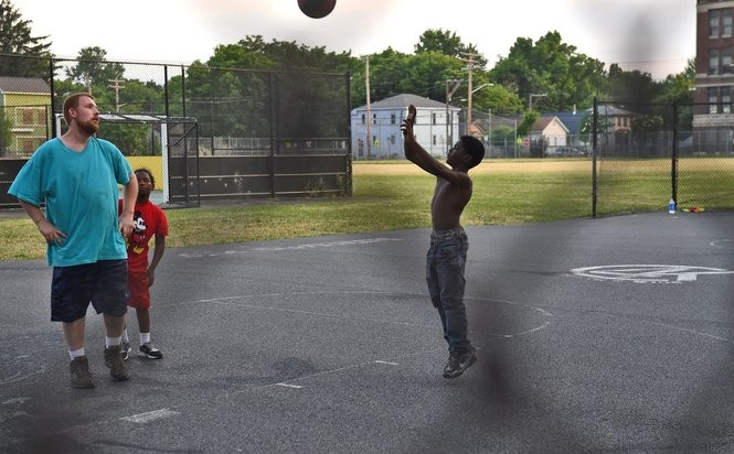 Eric Barden, at left, shoots hoops with Azar'yon Leslie and Kendell Pringle at Skiddy Park on Syracuse's Near Westside, Monday June 20, 2016.