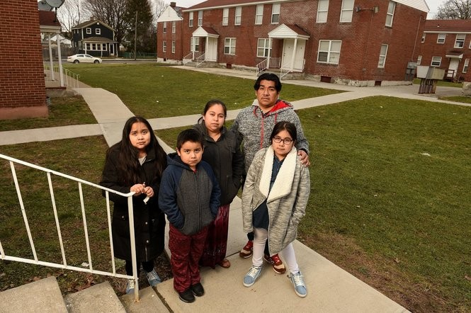 Hector Navarro and his family stand in the courtyard of their apartment in Syracuse. They are L to R Lisania, Angel Jesus, mother Arely Tomas Orazco, Hector and Karin, February 24, 2018. Michael Greenlar | mgreenlar@syracuse.com