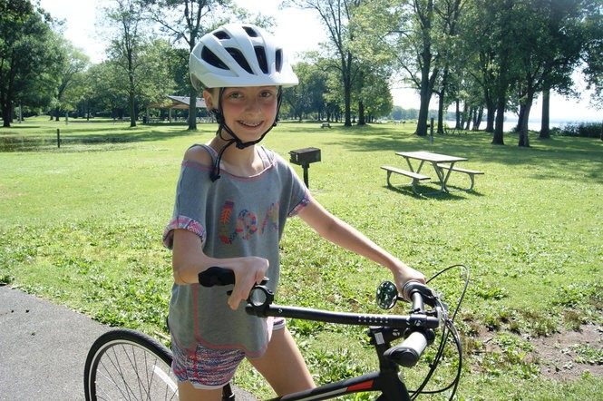 Maria Francescotti stands with her new bike, designed special for her by Syracuse Bicycle