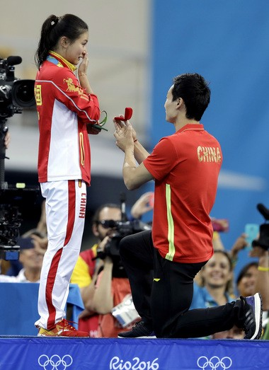 China's silver medalist He Zi, left, receivers a marriage proposal by China's diver Qin Ki, right, during the medal ceremony for the the women's 3-meter springboard diving final in the Maria Lenk Aquatic Center at the 2016 Summer Olympics in Rio de Janeiro, Brazil, Sunday, Aug. 14, 2016.