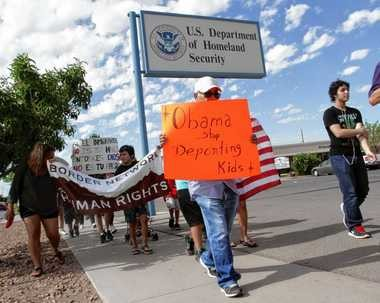 Marchers held signs as they made their way to Department of Homeland Security offices, protesting immigration policies Thursday, July 10, 2014, in El Paso, Texas.