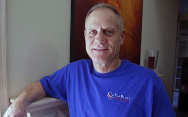 In this Feb. 16, 2018, photo, Andy Cilek poses with a Tea Party shirt at his home in Eden Prairie, Minn. Cilek was one of two voters who defied elections officials after he was asked to cover up a tea-party shirt and button. The Supreme Court has struck down a Minnesota law that restricted what voters can wear to polls. The justices ruled June 14, that the law violates the First Amendment.