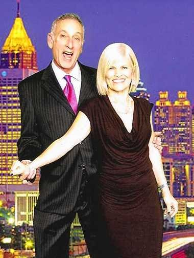 Dave Cohen and his wife, Kathleen, pose in front of an image of the Atlanta skyline.