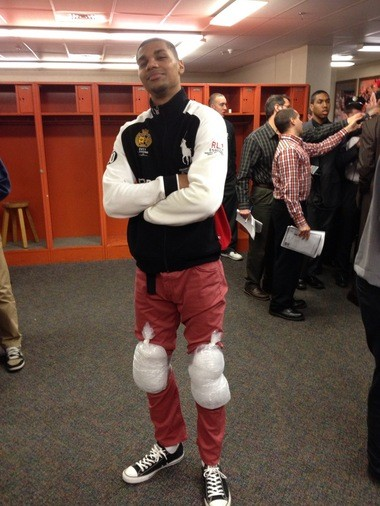 Michael Gbinije wears Jerami Grant's clothes and ice packs on his knees for an Orange game last winter.