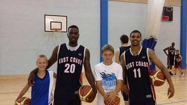 Rakeem Christmas and Michael Gbinije pose with kids from Estonia after their East Coast All Star team played an exhibition game on Tuesday.