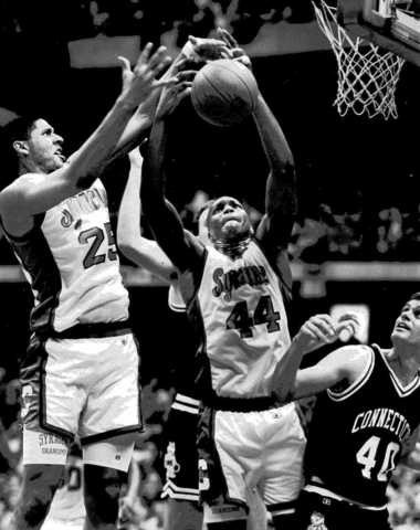 Syracuse's LeRon Ellis and Derrick Coleman go after the ball as Connecticut's Nadav Henefeld looks on during a game on Feb. 10, 1990, at the Carrier Dome.