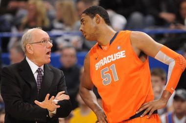 Syracuse head coach Jim Boeheim has a talk with Fab Melo in the Orange's game against UConn in 2011.