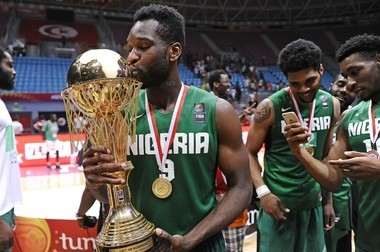 Champ Oguchi holds the AfroBasket 2015 trophy, while Michael Gbinije and Andy Ogide capture the moment.