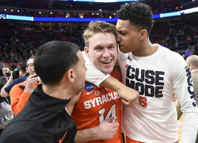 Braedon Bayer (center) celebrates with teammates Matthew Moyer (right) and Ky Feldman (left) after Syracuse's win over Michigan State in the NCAA Tournament.