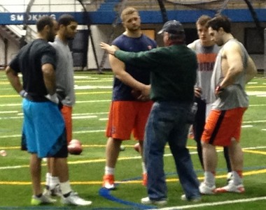 Paul Hackett, back to camera, offers instruction to a group of Syracuse players working toward pro day on March 7. Clockwise from left: Alec Lemon (blue shorts), David Stevens, Zack Chibane, Ryan Nassib, Carl Cutler.