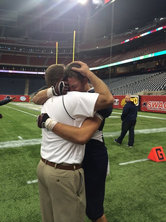 Koda and Kirk Martin embrace after their final high school football game together ended in a quarterfinal loss in the state playoffs at NRG Stadium in Houston.