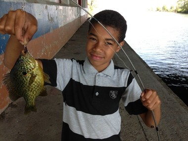 Yamil Rivera, 10, of Baldwinsville, holds up a nice pumpkinseed he caught on a worm.