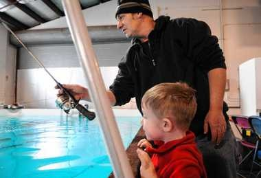 Dennis Wasiewski, of Owasco, fishes with his son, John, 3, in a trout pond set up in the Center of Progress Building at the state fairgrounds Friday for the 58th annual Northeastern Sport Show in 2011. It was presented by The Friends of Carpenter's Brook Fish Hatchery.