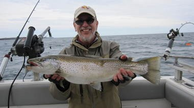 Outdoors writer David Figura with a 7-pound brown trout he caught aboard Capt. Tony Buffa's boat on Lake Ontario near Oswego.