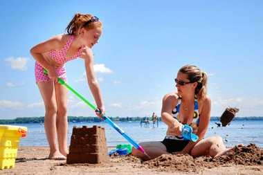 Lexis Harmer, 8, of Hastings, helps fill the moat for a sandcastle she and her mom, Krissy, built Friday at Oneida Shores County Park. This photo was taken in 2011.