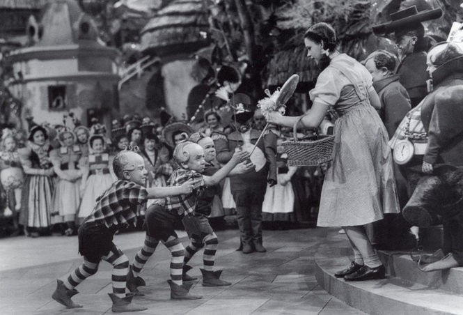 Jerry Maren, playing a Lollipop Guild Member, presents Judy Garland with a lollipop in the 1939 film 'The Wizard of Oz.'