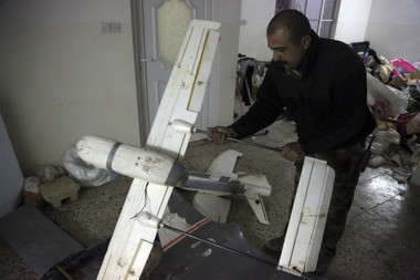 In this Friday, Jan. 27, 2017 photo, an Iraqi officer inspects drones belonging to Islamic State militants in Mosul, Iraq. Islamic State is hacking store-bought drone technology, using rigorous testing and tactics that mimic those used by U.S. unmanned aircraft to adapt to diminishing numbers of fighters and a battlefield that is increasingly difficult to navigate on the ground. (AP Photo/ Khalid Mohammed)