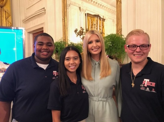 Ivanka Trump poses in the White House East Room with recent Syracuse high school graduates, from left, Robert Felder, Lilly La and William DeJesus on Thursday, July 19, 2018 in Washington.