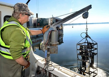 Bruce Wagner, of the Upstate Freshwater Institute, hauls up a sensor that measures the concentration of calcium nitrate being injected into Onondaga Lake by contractors on the barge in background.