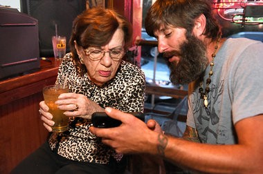 Ike Isenhour shows Marge a picture on his phone at Shifty's open mic on Wednesday, July 30, 2014.