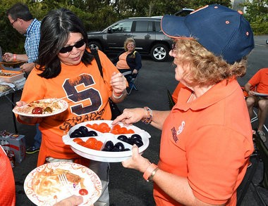 """Sue Conners of Solvay serves up football helmet-shaped Jell-o shots to Alice Lee of Pinehurst, N.C. The """"Fine Mess"""" tailgate set up shop in the Fine parking lot, drawing attendees from North Carolina, Tennessee and Nebraska on Friday for Syracuse's game against Louisville."""