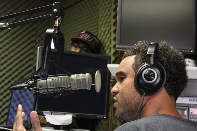 "Scott ""Big Slim"" Johnson on air during a recording of ""Live from the Box"" on Wednesday, May 13, 2015. In the background is producer Arion Mims."