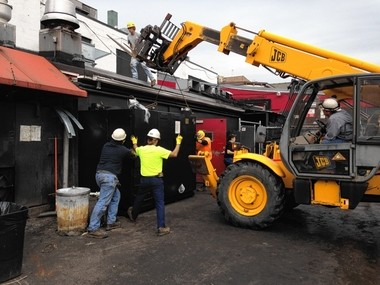 A new 1-ton smoker being loaded into the smokehouse behind the Dinosaur Bar-B-Que at Willow and North Franklin streets in Syracuse.