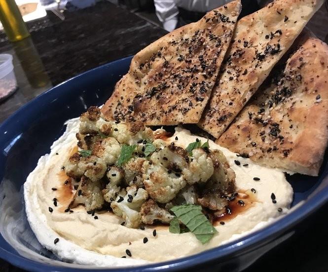 Hummus with yogurt, cauliflower, pomegranate vinaigrette, and za'atar pizzette a amano kitchen & bar in Syracuse.