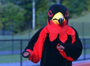 A Fowler High School mascot dances at a home game that was held at Corcoran High School's athletic field Sept. 25. The Fowler Falcons are in their sixth season without a field on school grounds.