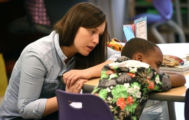Dr. Weeks Elementary School second grade teacher Courtney Marx talks to one of her students after a reading session.