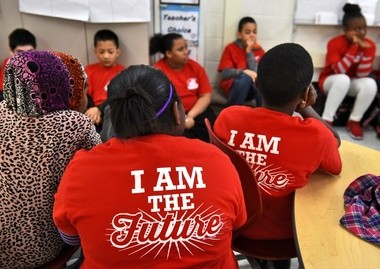 """On Mondays, students at Dr. Weeks Elementary School wear T-shirts with their school name on the front and """"I AM THE FUTURE"""" emblazoned on the back. Teachers' shirts say """"relentless"""" on the back."""