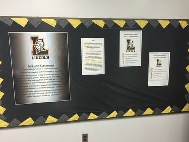"""Lincoln Middle School's goals and rules are taped on the walls to create clear expectations for students. Teachers can also use the displays for """"non-verbal redirection,"""" so if a student is breaking a rule, they don't have to stop class, but can just make eye contact and point."""