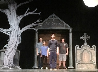 "Members of the ""The Addams Family"" cast in front of the family crypt are left to right, Ben Blackwell as Lurch, Sierra Sander as Wednesday, Calvin Blackwell as Gomez and Tyler Atwater as Fester."