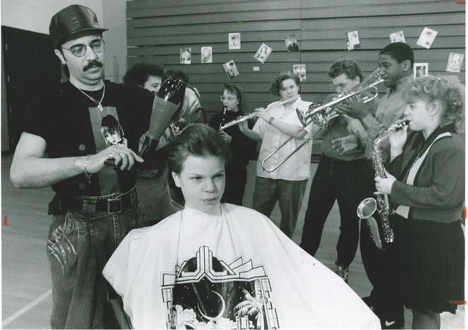 A hair-cut-a-thon was held at Fowler High School on April 5, 1992 to benefit the school's jazz band. Jose Lopez of Umberto's hair Salon works on Patricia O'Connell, while the band warms up in the background.