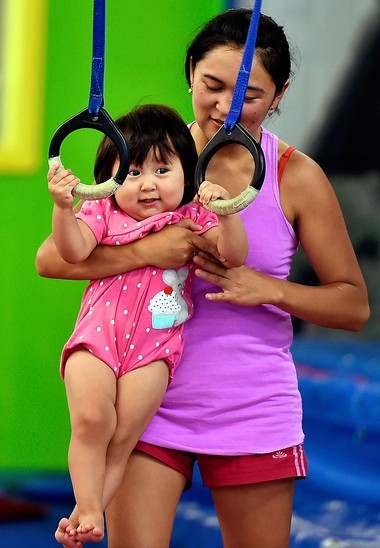 Genera Sultanaliev, of Syracuse, helps her daughter, Madina, 18-months, on the rings during the Parent & Tot.